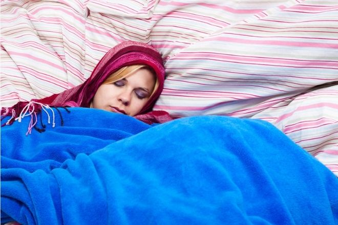 a new mom sleeping snuggled up with a heavy blue blanket on cozy looking sheets
